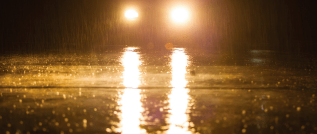 car on wet road at night, view of headlights