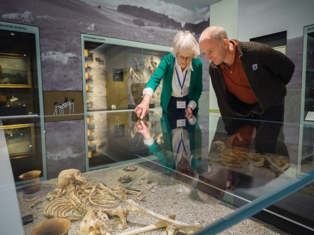 A Woman and a man look at a skeleton in a glass case. The woman is pointing to a part of the skeleton.