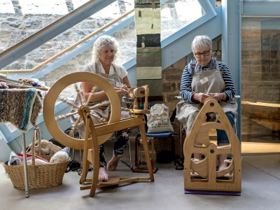 Two ladies with wooden yarn making machines