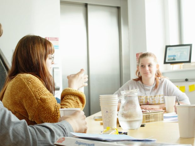 Young volunteers have a meeting around a table