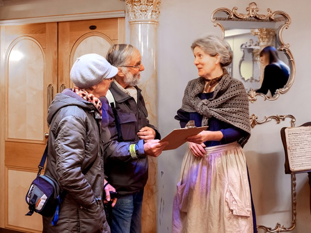 Two visitors talk to a museum team member in period clothing