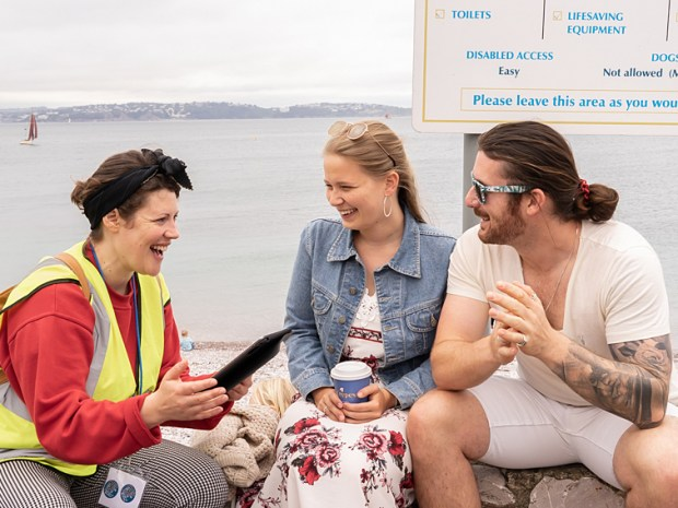 A woman with a high vis jacket holds an ipad, sits outside smiling with two people