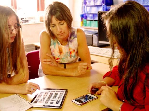 Three people sit at a table, looking at an ipad