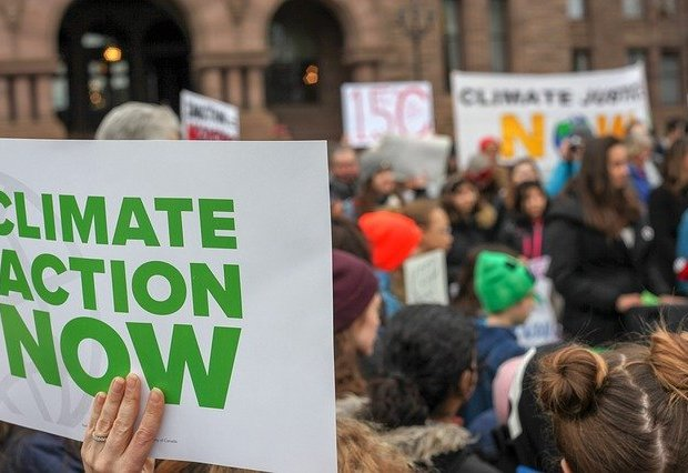 A protest, with a placard in the foreground stating 'climate action now'