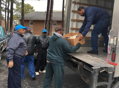 Boys to Men members unload the food truck.