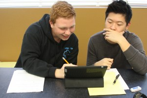 Juniors Eric Feldman and Alan Yuan play games on their I-Pad after school in Mrs. Tawanna Ervin's class during a quick break.<br /> Photo Credit: Hailey Basner