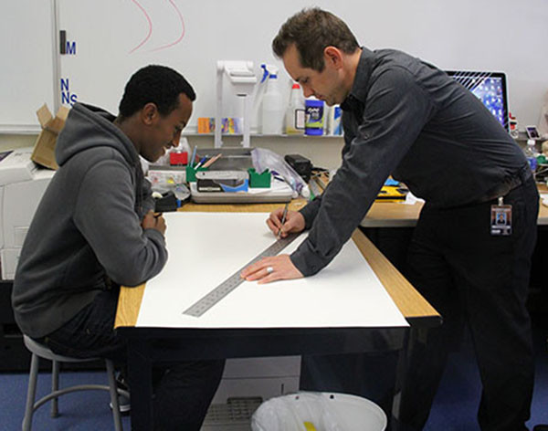 "Mr. Jared Ogden teaches senior Mehaki Asare how to draw perspective on a one-on-one level. ""I guess it's easy to draw perspectively, but it's actually kind of confusing to,"" Asare said.  Photo Credit: Jenika Chiang"