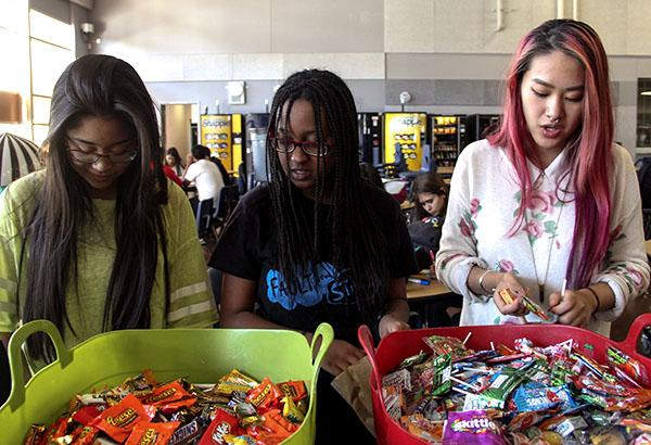 "National Honor Society members Rein Villahermosa, Sibriya Said and Huilin Chen work as a team to assemble trick-or-treat bags to donate to the Shade Tree Organization. Roughly 200 bags were made and will be delivered to the shelter the following week by the officers. ""It feels really good that I was able to help our local community. Our community is what shapes us,"" Said said.   Photo Credit: Shamaeka Pagado"