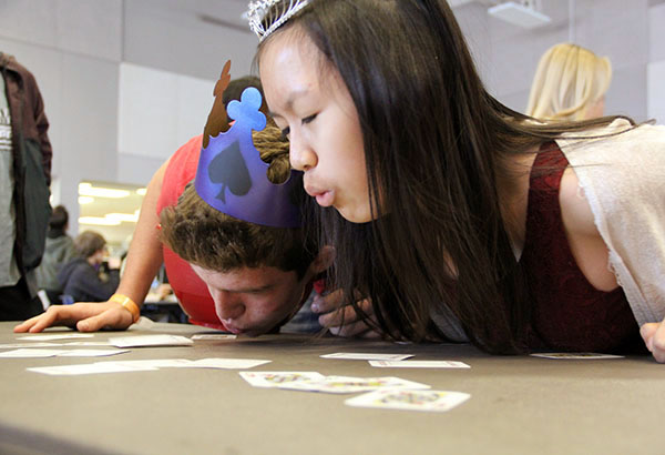 Freshmen Justine Ho and Rodney Krantz compete against each other in the lunch game during second lunch. The goal of the game is to blow all of the cards off of table and leave only the King of Spades or Queen of Hears cards face-up.  Photo Credit: Jorge Carrera