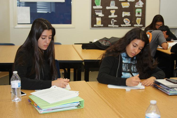"Reading the packet along with the speaker helps juniors Janessa Montenegro and Crystal Menjivar understand the main idea of the story. ""I grew up with people that spoke Spanish, but my parents never taught me so I took it upon my self and learned by myself,"" Montenegro said."