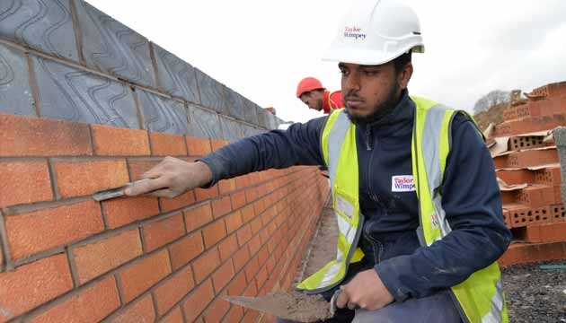 Harpreet working on a large red brick wall