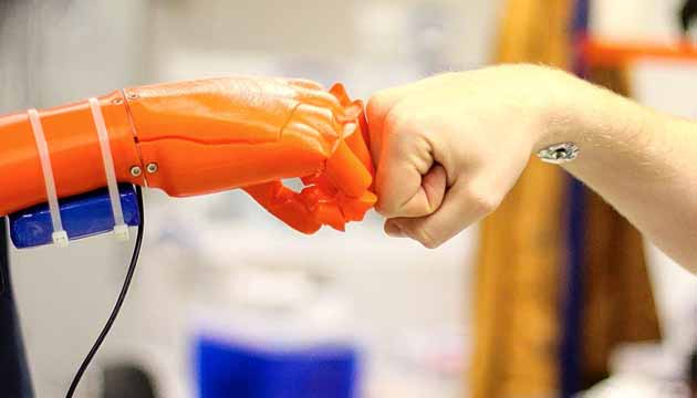 One of its developers demonstrates a robotic arm by giving it a fist bump