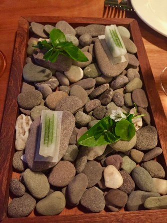 Radishes and locally foraged greens, served on a plate of rocks from the local beach