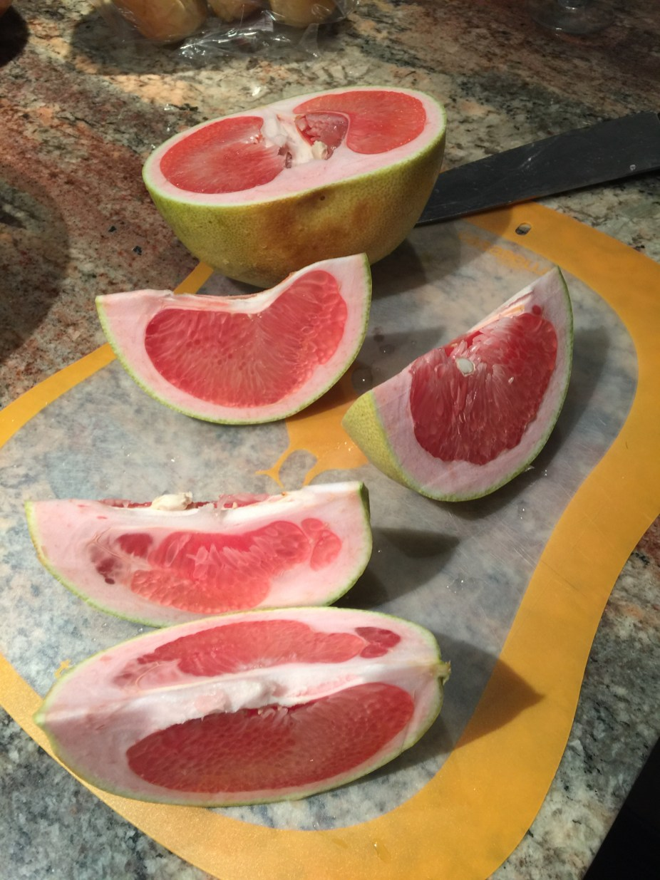 Inside a pomelo, like a sweeter grapefruit