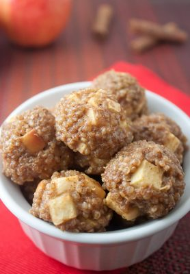 Apple Cinnamon Quinoa Bites in a small bowl with cinnamon sticks and an apple in the background