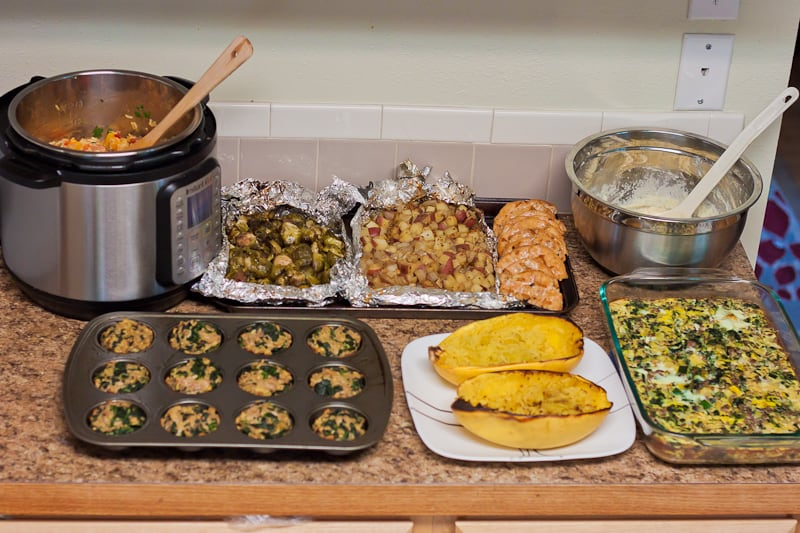 A week of meal prepped food on a counter- roasted spaghetti squash, grilled foil packets, mashed cauliflower, turkey meatloaves, etc