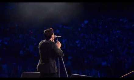 Robbie Williams jugando con los flashes de las cámaras en un concierto