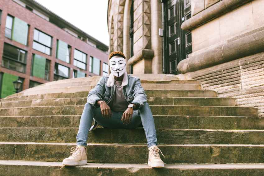 black man in anonymous mask sitting on stairs on street