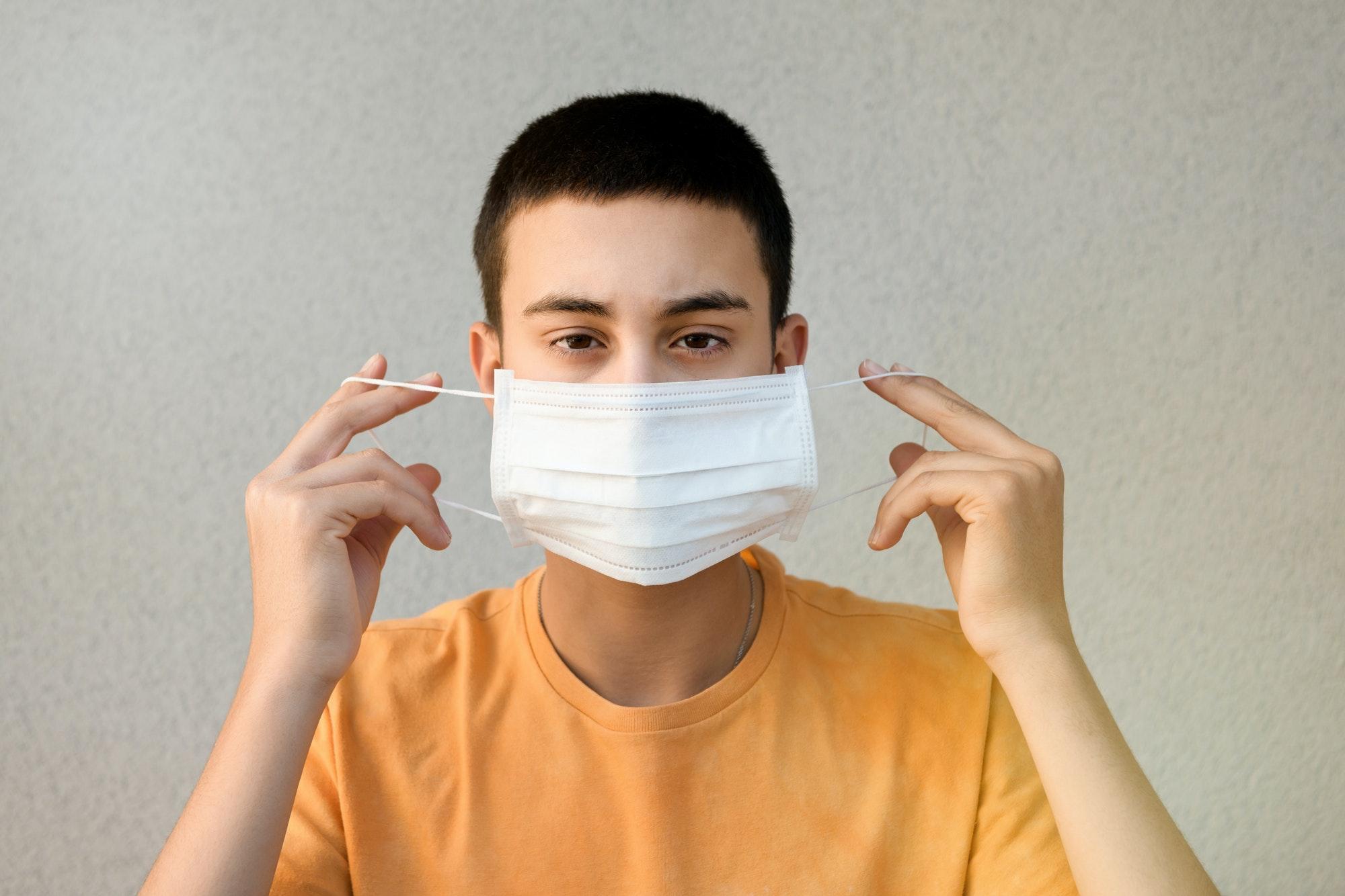 Niño adolescente sosteniendo una mascarilla