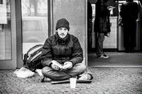 """Zu sehen ist ein junger Mann mit Mütze, der im Schneidersitz im auf dem Bürgersteig sitzt. Vor ihm ein Becher, in dem er Geld sammelt, hinter ihm sein Gepäck. Das Bild ist schwarz-weiß und Teil der Ausstellung """"Kein Raum"""" von Debora Ruppert. Von ihm stammt das folgende Zitat."""