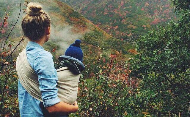 мама и ребенок в слинге смотрят на горы