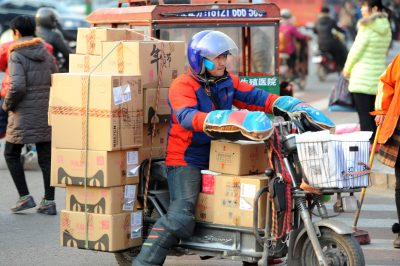 A Chinese courier rides a motorcycle to deliver parcels, most of which are from online shopping, Huaian city, China, 12 February 2015 (Photo: Reuters)