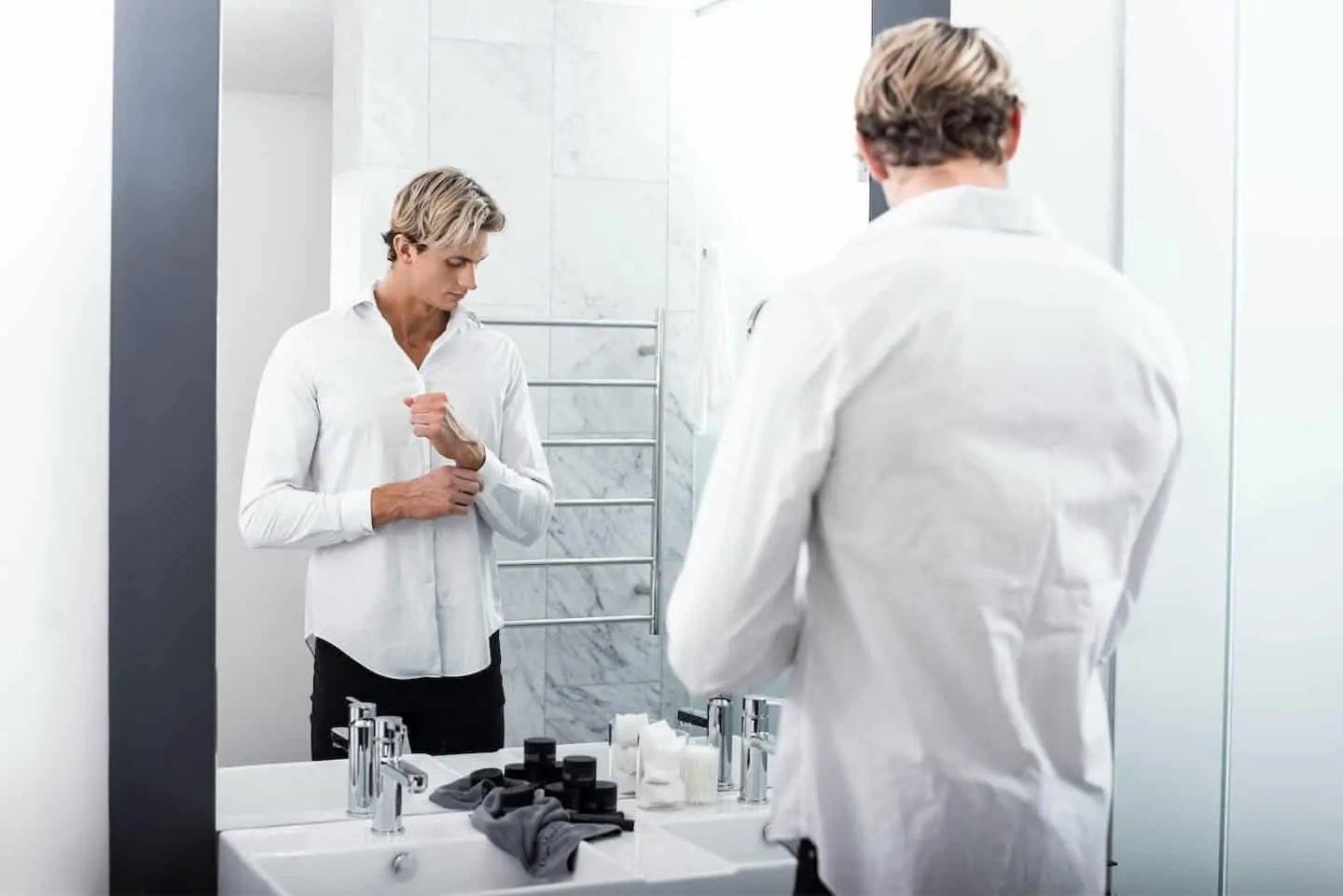 Man standing in front of mirror in white shirt buttoning cuffs
