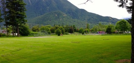 Large grass playground field stretching from North Bend Elementary to Two Rivers High School along 3rd Street in downtown North Bend.