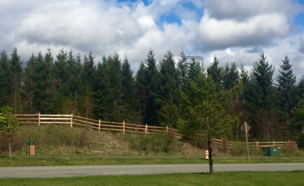 DOC crews rebuilt fence surrounding large retention pond next to Snoqualmie Parkway.