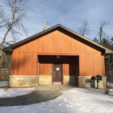 A wood sided restroom building with outside drinking water fountain