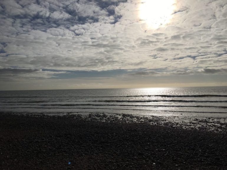 The sun shining through white clouds reflected on the sea water.
