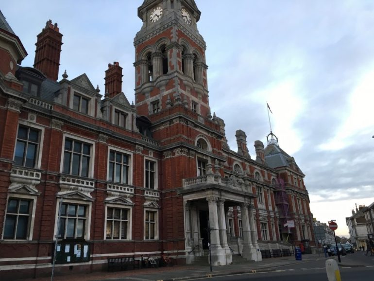 An enormous brick building, complete with decorative columns and an ornate clock tower.