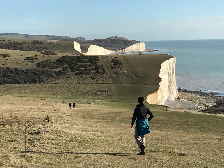 A smattering of hikers walking un and down grass covered hills along the cliffs overlooking a vast body of water
