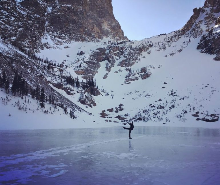 Dancer posing in winter gear on the frozen Emerald Lake surrounded by snow covered mountains