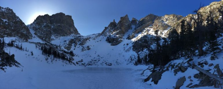 A large frozen lake encircled by tall jagged snow-covered mountain peaks.