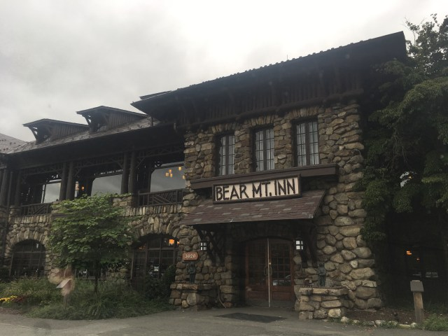 The Bear Mt Inn is a stony lodge with big wooden double doors and a rustic sign