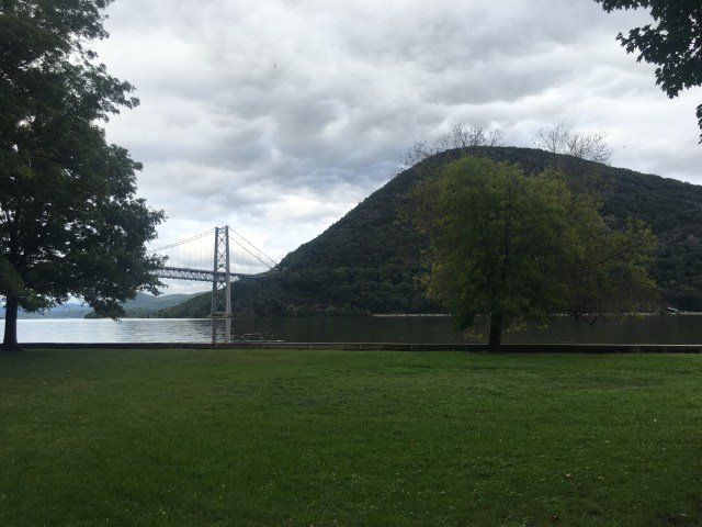 A water level view of the Hudson River, the bridge and the mountain peak across the shore
