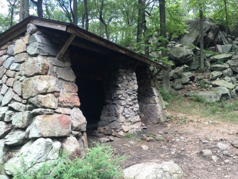 Stone 3 wall shelter located beside big rock boulders on the trail