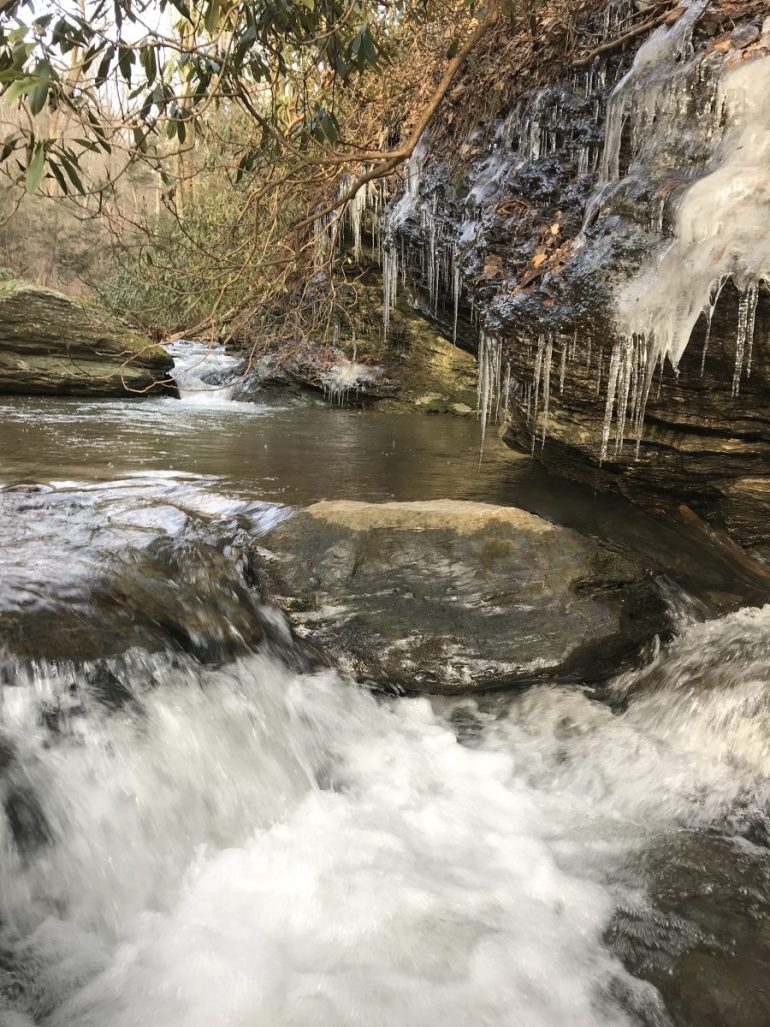 Churning waterfall in the foreground, large icicle covered rock boulder hangs over the water, with another waterfall in the distance.