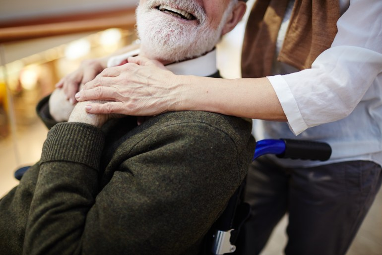 Older man in a wheelchair, smiling and holding hands with a female caregiver