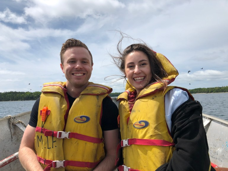 Man and woman in their twenties sitting in a small boat, wearing yellow life vests and huge smiles