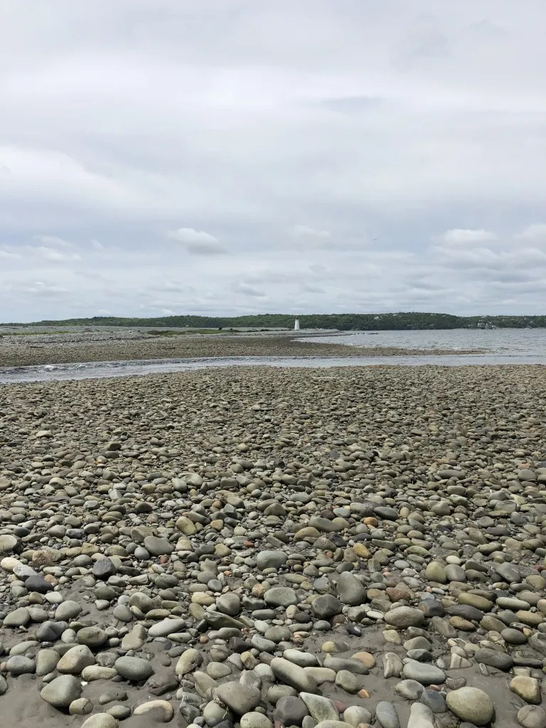 Cobble stones cover the beach and a small white lighthouse is visible in the distance