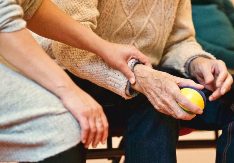 Caregiver seated beside an older man who is holding a small ball; her hand is on his arm for encouragement.