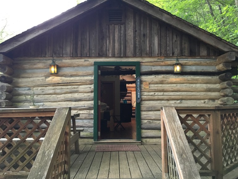 An upclose photo of a log cabin, with its door open.