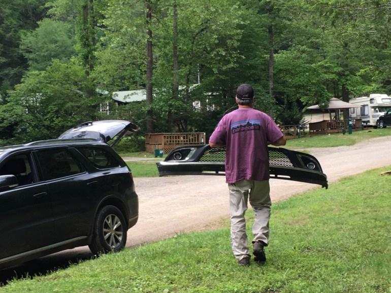 A man walking away carrying a car bumper