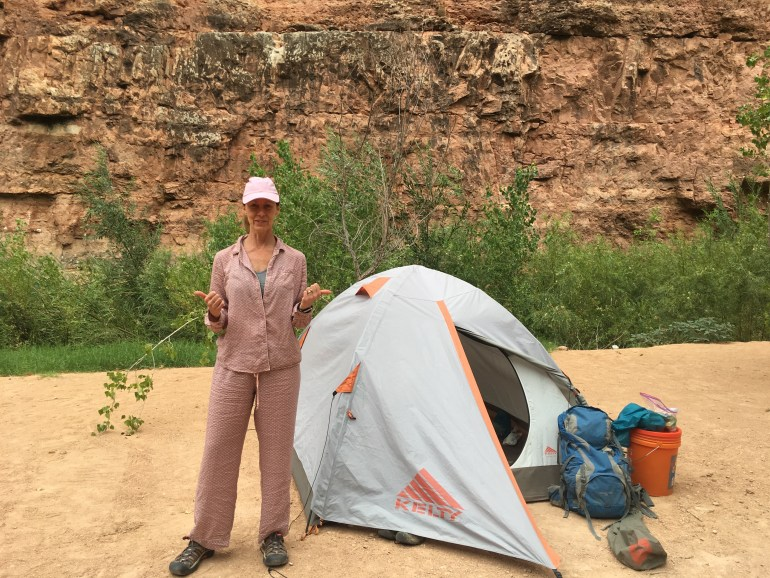 A woman in pink pajamas standing beside her tent and backpack