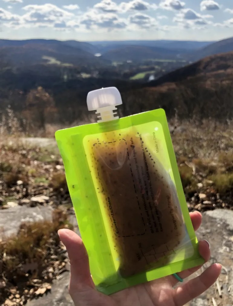 A food pouch in a hand, a Mountain View in the background