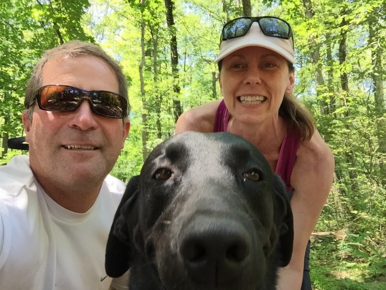 Man, woman and black Labrador posing for a selfie.