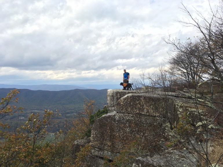 A man with a black lab, standing on a rocky outcropping that overlooks mountains and valleys.