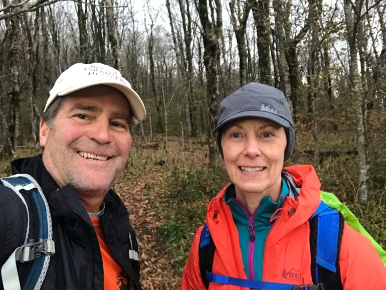 A man and woman hiking couple posing in the woods